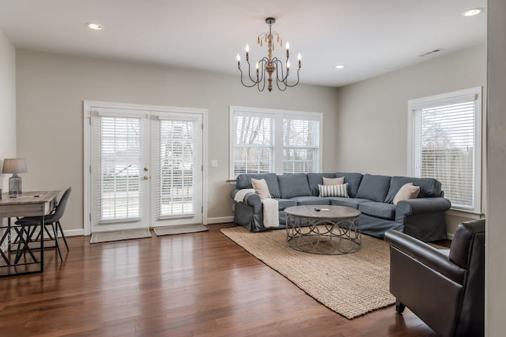 Large living area with 65 inch wall flat screen tv and french doors leading to large back deck