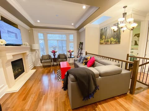 """Living room with 55"""" smart Tv, windows facing the North Vancouver mountain views."""