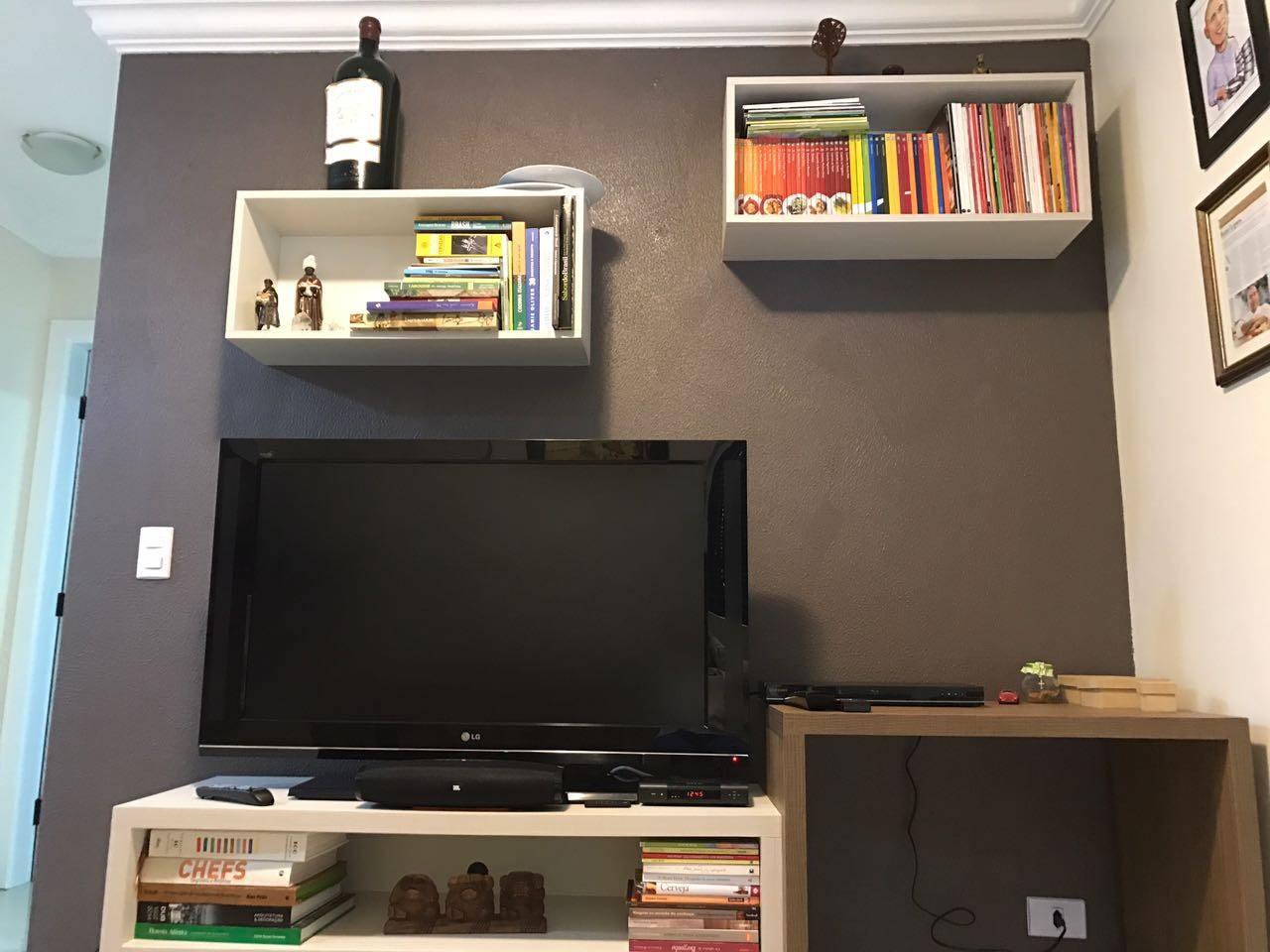 Sala com TV a cabo e pequena escrivaninha