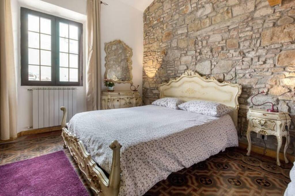 Ampia e luminosa camera, arredamento classico, con pareti in pietra e pavimento tradizionale.