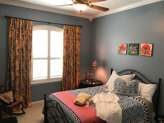 1st Guest Bedroom. Very comfortable Queen size bed with pillow top cover and pure cotton bed linens. Ceiling fan for cool quiet breezes and room darkening drapes over shutters. Speaker for music-provided-no TV currently.