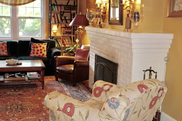 A comfortable social space with ceiling fans, sunny window views, and a wood-burning fireplace.