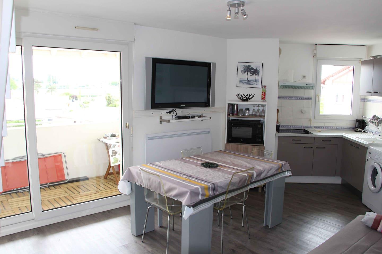 Le séjour avec cuisine et terrasse.