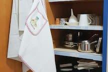 Uno dei pensili della cucina con tutto l'occorrente riposto negli scaffali con  apposite etichette bilingue (in italiano e inglese)