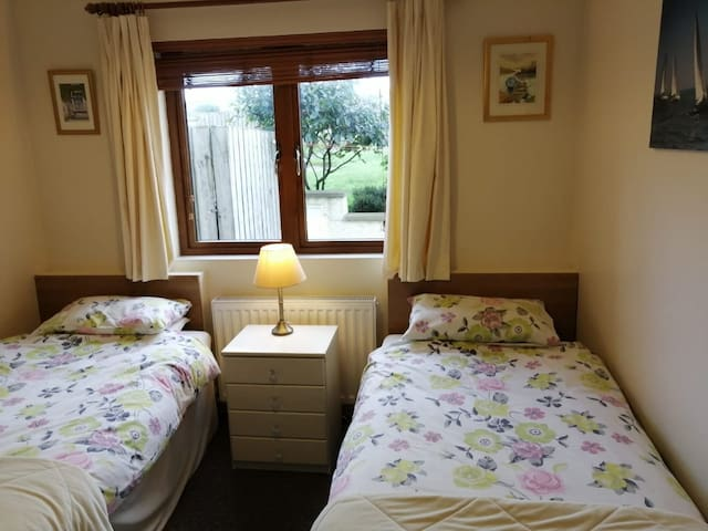 Comfortable Twin room to rear of apartment with wardrobe and chest of drawers, including large mirror.