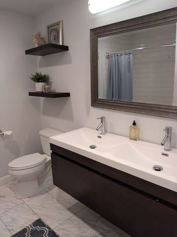 Large bathroom with two sinks and over sized bathtub.