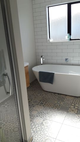 guest bathrooom with full size shower bath and vanity