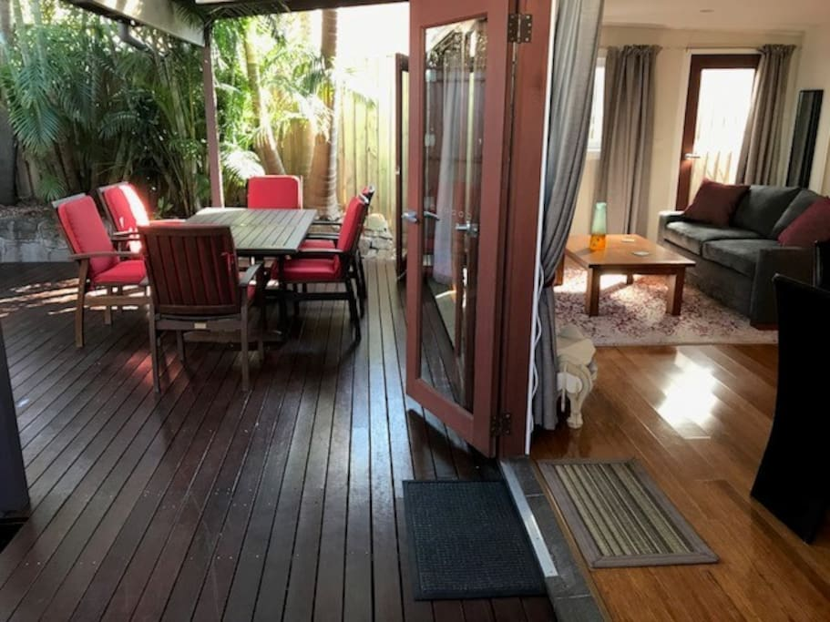 Indoor space opening onto private oasis deck in palm garden