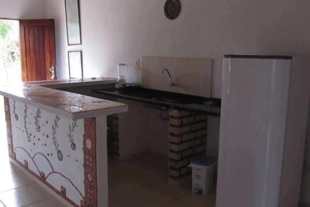 Cozinha com fogão, geladeira e utensilios