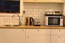 Kitchenette with tea, coffee, toaster, kettle, microwave, electric wok & breakfast items