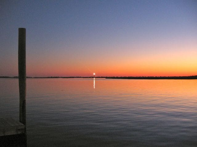 Oak Island Lighthouse at Sunset viewed from dock in Southport