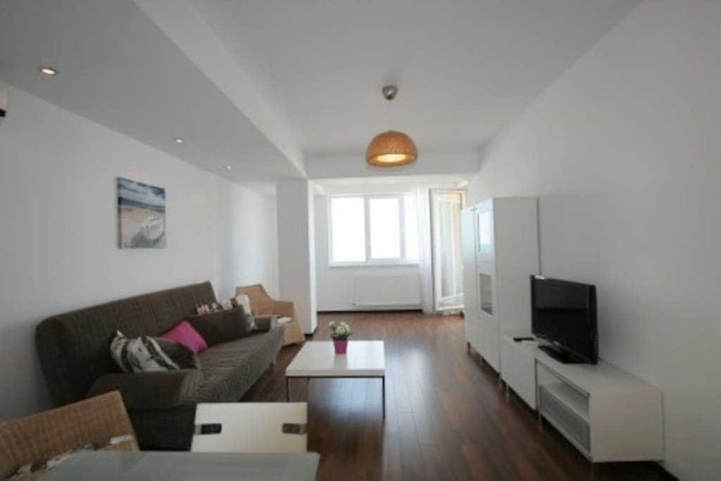 The living rom is open space and is equipped with sofa bed, Tv, table with chairs and air conditioning.