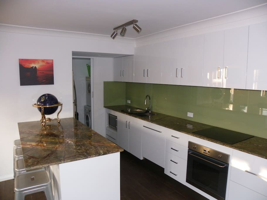 Designer kitchen with integrated dishwasher, pyrolytic oven, induction cook top and marble bench tops.