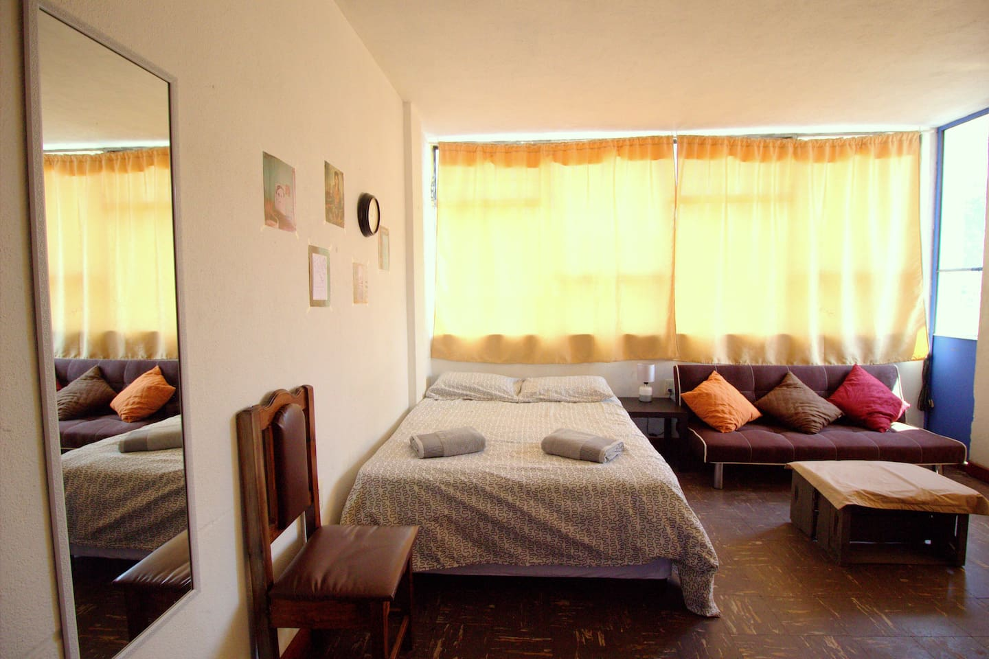 Your room with one double bed, a sofa, chairs, a table and a TV.
