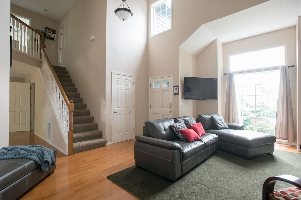 Living room area with TV and stairs to 3 bedrooms upstairs