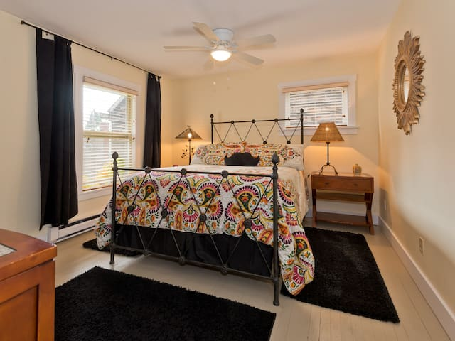 #1 -Large Bedroom, Queen Bed ,showing SUMMER Bedding.  Room has large dresser/mirror, TV, closet and black out curtains