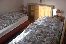 Zweites Schlafzimmer mit zwei bequemen Einzelbetten und einem Kleiderschrank