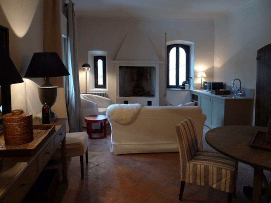 il soggiorno con caminetto d'epoca e cucina/the living room with original fireplace and kitchen