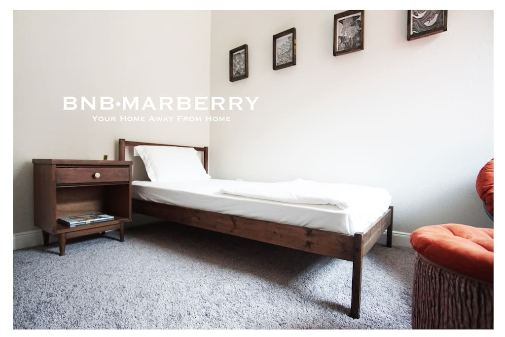 Single bed in a private room with a pretty antique nightstand.