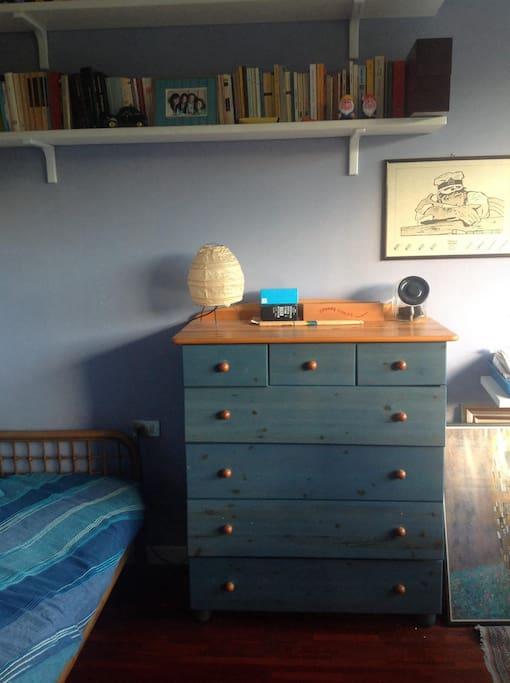 Il cassettone a disposizione dell'ospite, con cassetti capienti. In alto a sinistra un'altra abat-jour con una presa elettrica vicino al letto dell'ospite.