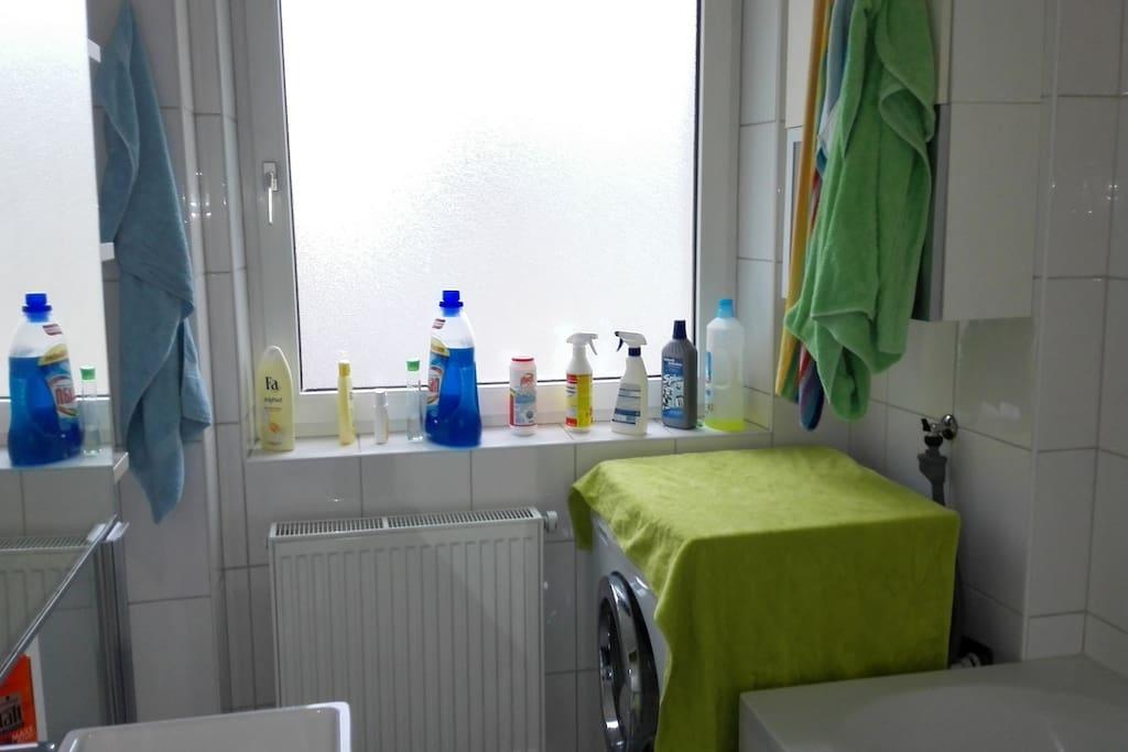 Helles Badezimmer mit Waschmaschine und extra Badewanne.