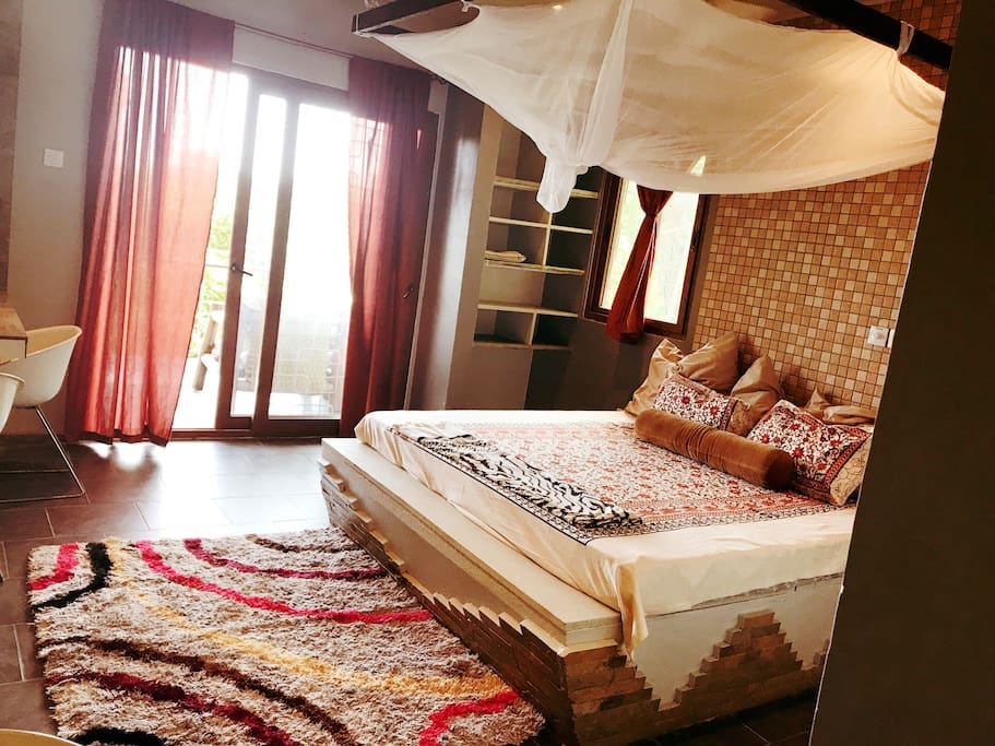 King size bed with a mosquito net and ceiling fan. French doors leading on to a private balcony. The room is open, airy, bright and cheerful.