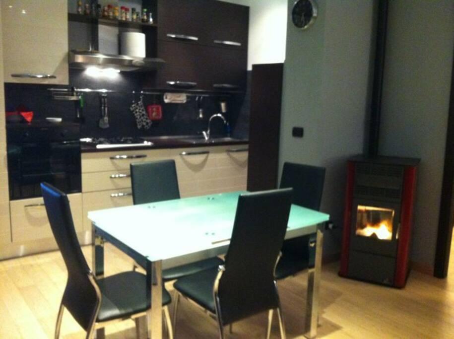 Vista del soggiorno con stufa a pallet e della cucina.