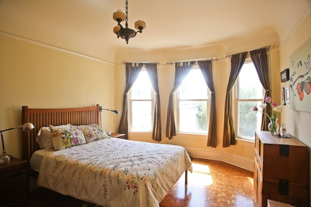 Spacious sunny master bedroom with queen bed