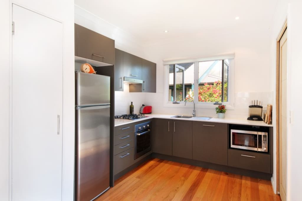 Contemporary Kitchen with integrated dishwasher with  separate laundry on right.