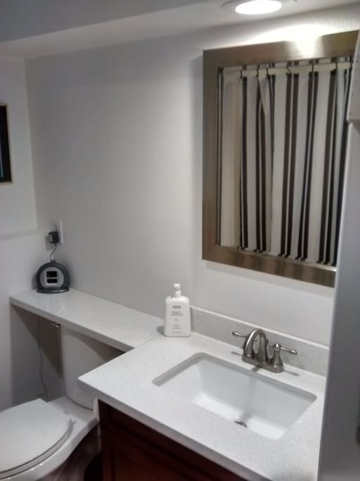 Private 3/4 bath with quartz counter top and tile floor.