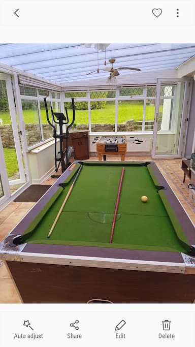Pool table in conservatory games room with patio doors to external garden area
