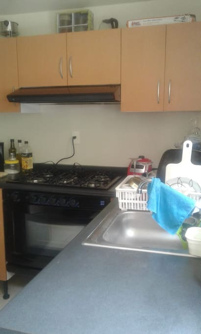 Cocina con refrigerador y microondas y utencilios