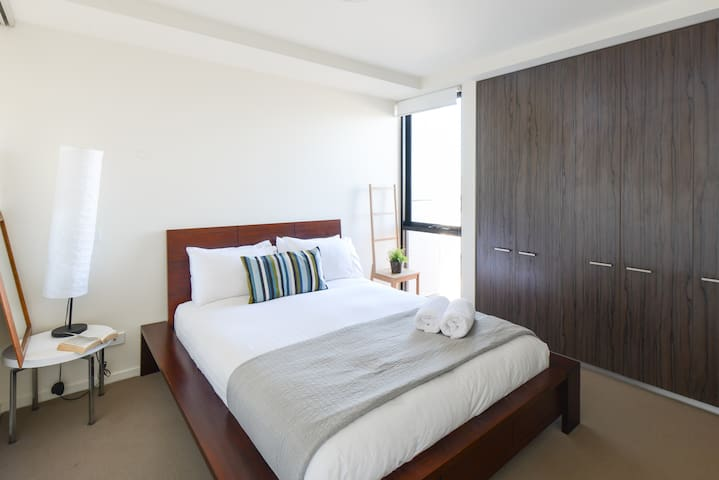 A well-lit bedroom comes furnished with a plush queen bed surrounded by bedside tables and built-in wardrobes