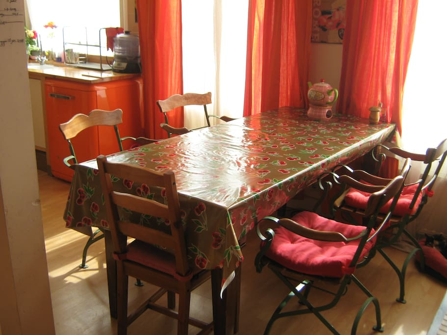 Dining table with the orange dishwasser at the back