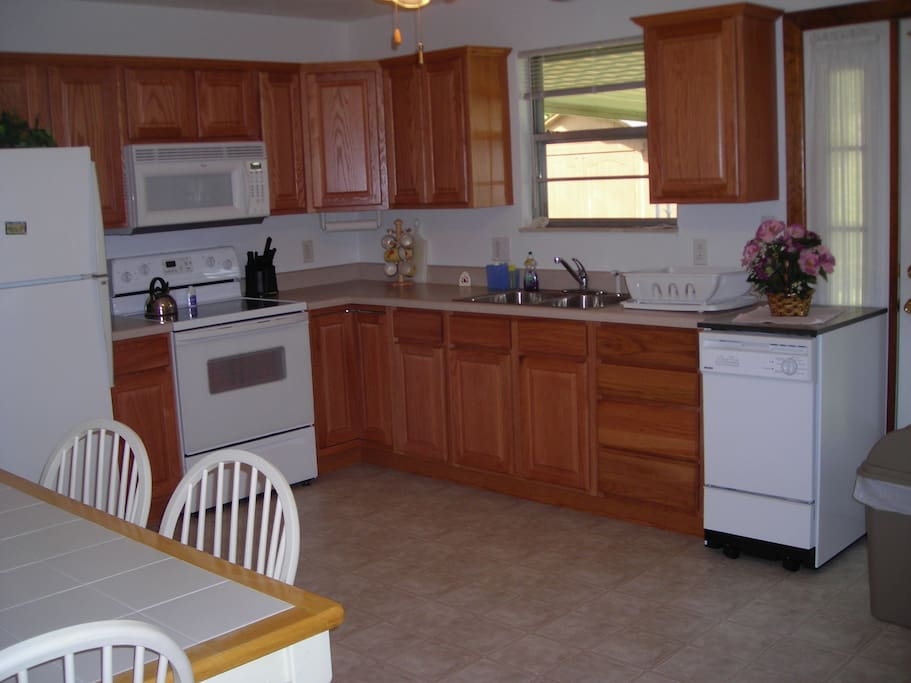 Remodeled kitchen with flat top cooking surface, dishwasher, garbage disposal and hidden full size washer and dryer