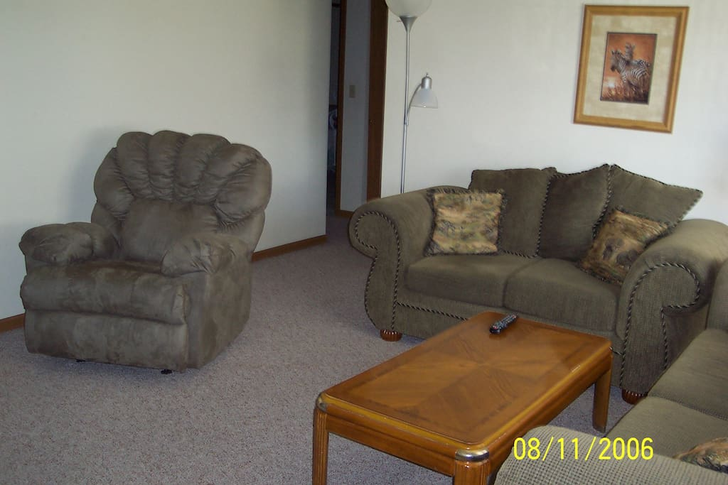 Bright living room with couch, love seat, recliner and large flat screen T.V.