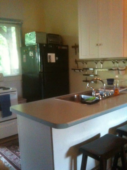 Kitchen with full fridge, electric stove, microwave, toaster oven and island with seating.
