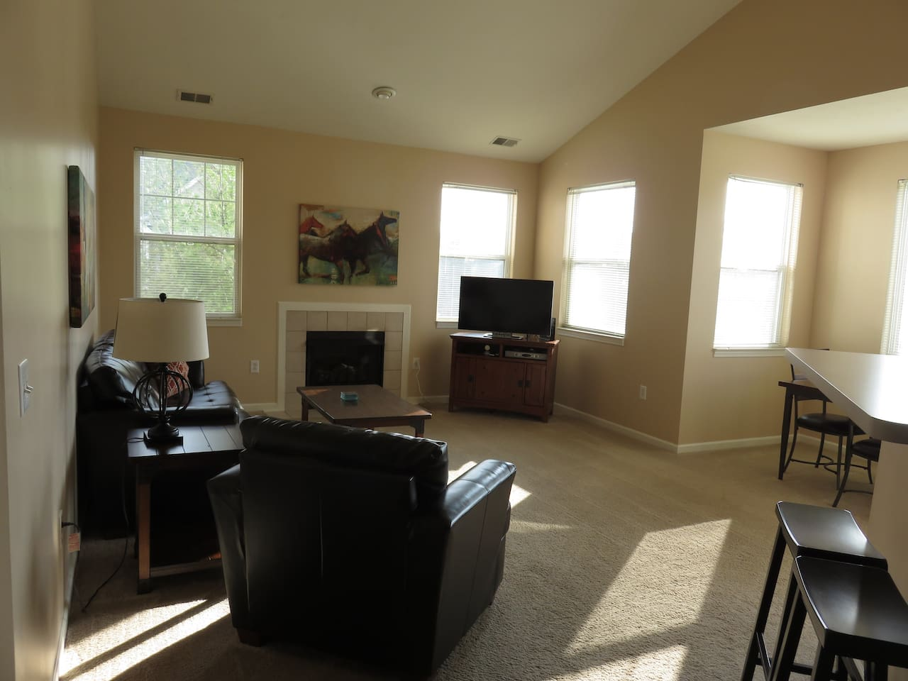 Spacious Family Room overlooks the golf course with vaulted ceilings, cozy fireplace and HDTV