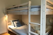 The second bedroom is suitable for up to two people. It has a garden view, built in closets and workspace. The room can fit an additional baby bed.