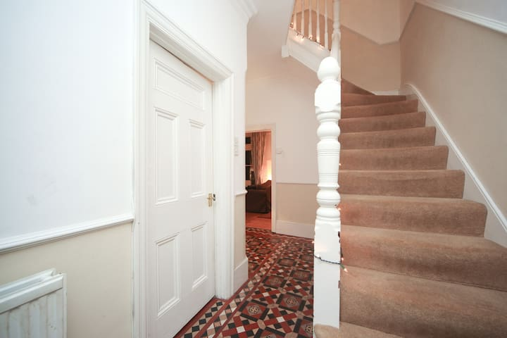 Stairs to first floor and a view into the lounge area