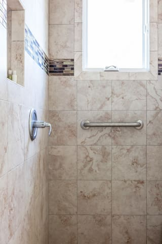 A roomy shower with hand rails.