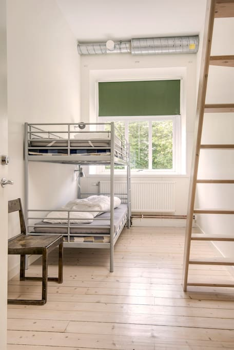 Room with a bunk bed and two beds on the loft.
