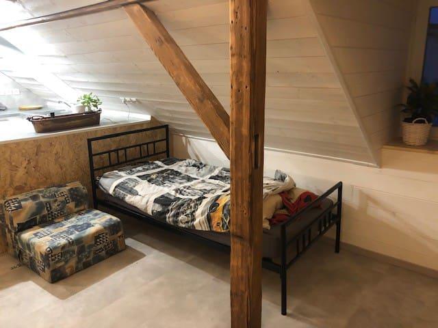 lit simple avec couette douillette, la chauffeuse est à côté, mais on peut l'ouvrir sur le tapis au salon pour plus d'espace .