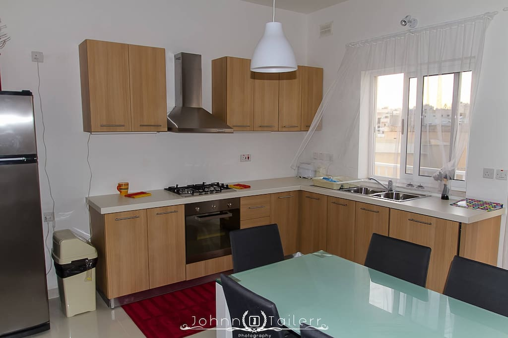 Modern kitchen with microwave and gas oven, dish washer and large fridge.