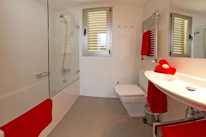 Fully equipped bathroom with shower, bathtube and hairdryer