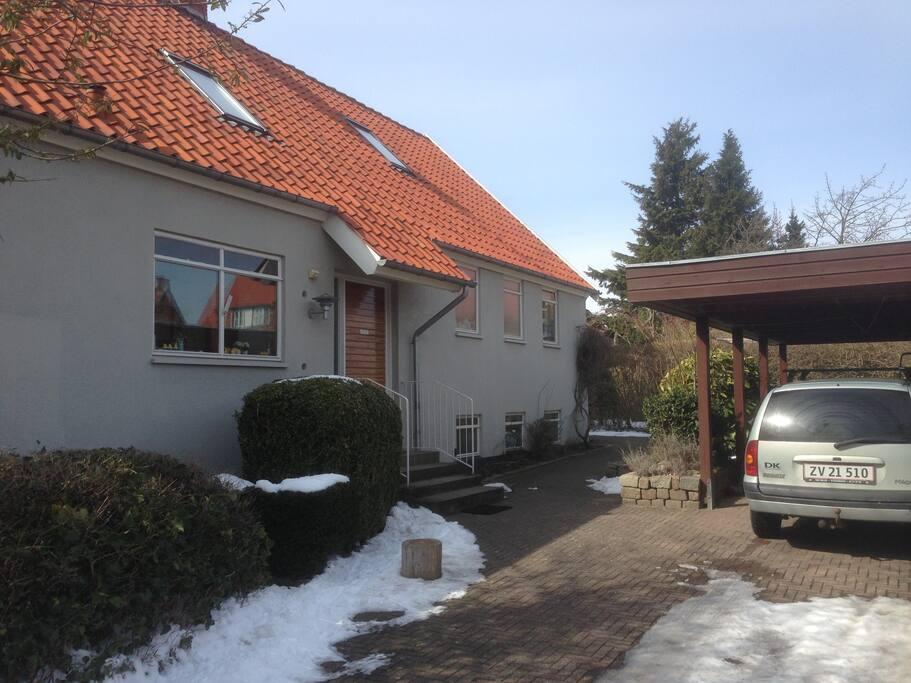 Huset set fra fronten med carporten.