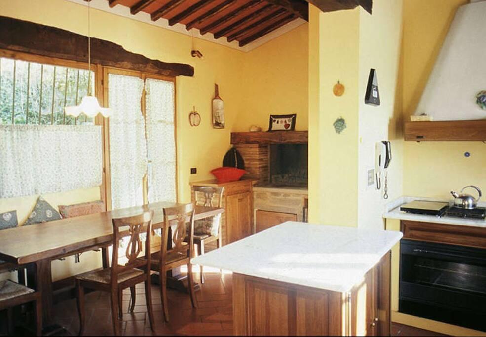 nella sala da pranzo adiacente alla cucina c'è un grande camino adatto per cucinare