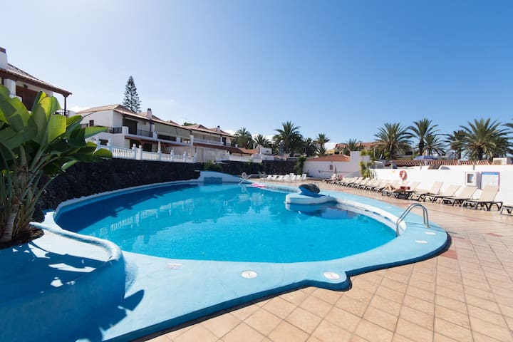 View of communal heated pool terrace with plenty of sun loungers available