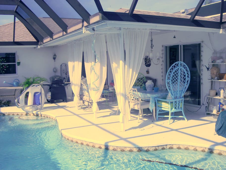Lanai, pool, dining area, seating area with lounge chairs.