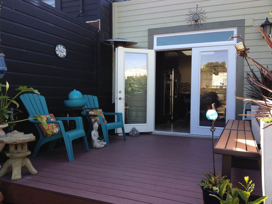 Back yard deck with double doors that lead to the kitchen